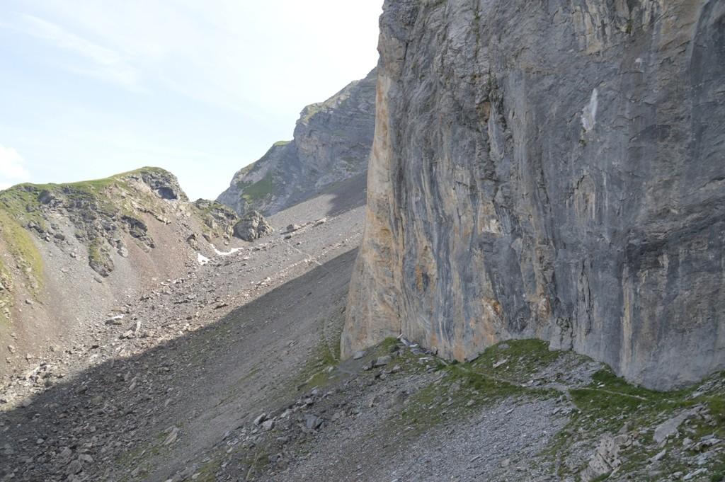 Longe dans l'ombre la base d'une falaise calcaire, puis monte dans un éboulis jusqu'à un petit col avant de se diriger vers Barroude au-dessus de la vallée de La Gela